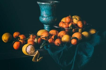 close up view of arrangement of fresh lemons and tangerines in strainer on table with dark tablecloth