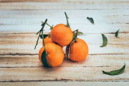 Photo pour Bouchent la vue de mandarines mûrs avec des feuilles sur une table en bois - image libre de droit