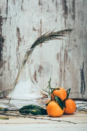 Nahaufnahme von Mandarinen auf leicht schäbiger Holzoberfläche mit Pflanze in Vase in der Nähe