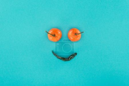 top view of tangerines and leaf arranged into smiling face isolated on blue