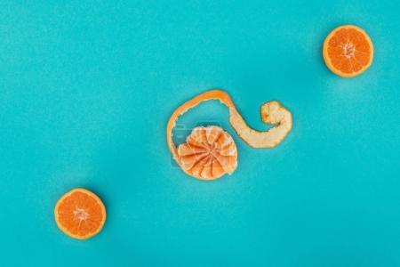 Photo pour Vue de dessus du mandarin mûr arrangé et morceaux d'orange isolé sur bleu - image libre de droit
