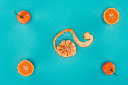 flat lay with ripe mandarins and orange pieces isolated on blue