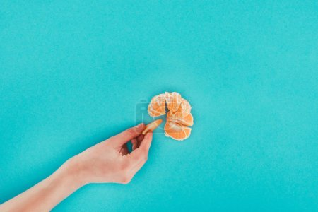 partial view of female hand and tangerine isolated on blue