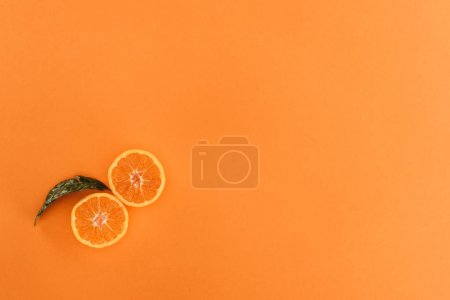 top view of pieces of orange and leaf isolated on orange