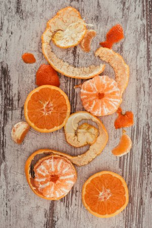 Photo for Top view of arranged mandarins, orange pieces and citron on shabby wooden surface - Royalty Free Image