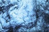 fond avec des tourbillons de peinture bleue dans l'eau