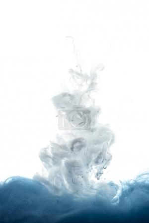 close up view of mixing of blue and white paint splashes isolated on white
