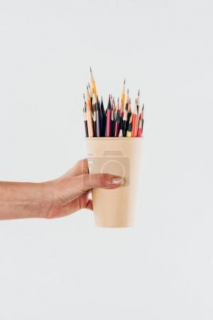 Close-up view of female hand holding cup with colorful pencils isolated on white background