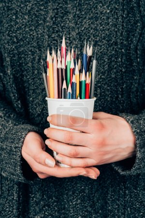 Close-up view of female hands holding cup with colorful pencils