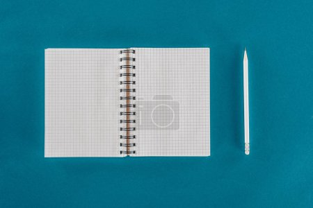 Top view of single pencil with blank notebook isolated on blue background