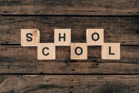 Top view of alphabet cubes with word school on wooden background