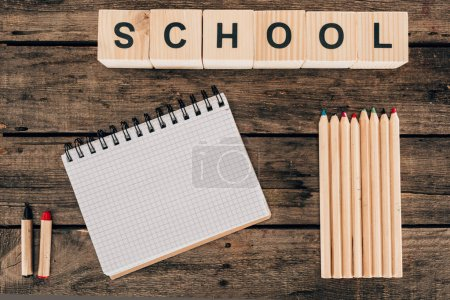 Top view of composition of colorful pencils with blank notebook and word school on wooden background