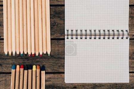 Photo pour Vue de dessus de composition des crayons colorés avec ordinateur portable blanc sur fond en bois - image libre de droit