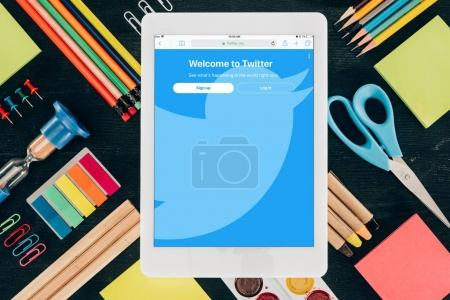 Flat lay tablet with Twitter app over background with school supplies isolated on dark