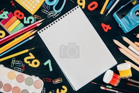Photo for Top view of composition of colorful school supplies with blank notebook isolated on dark board background - Royalty Free Image