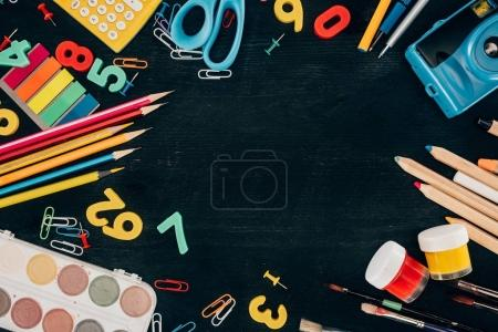 Top view of composition of colorful school supplies isolated on dark board background