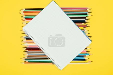 Top view of composition of colorful pencils with blank notebook isolated on yellow background