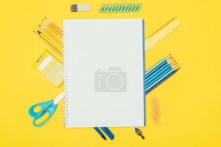 Photo pour Vue du dessus de la composition des fournitures scolaires colorées avec carnet vierge isolé sur fond jaune - image libre de droit