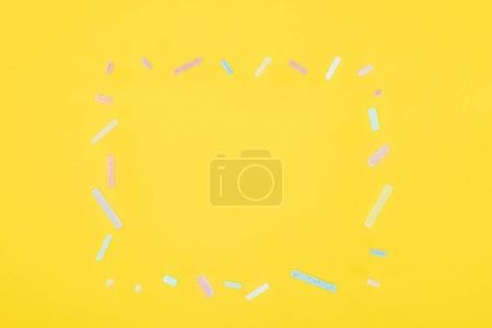 Top view of frame of colorful chalks isolated on yellow background