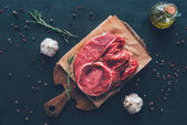 top view of raw steak on parchment paper and cutting board with spices around