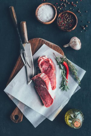 top view of raw meat slices on parchent paper and cutting board with cutlery