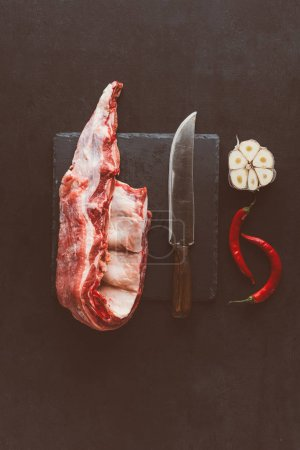 top view of raw pork ribs slice on stone slate with knife and spices