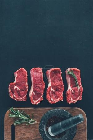 top view of raw steaks in row with spices on wooden board
