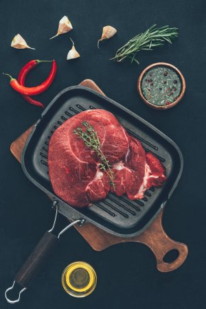 top view of raw steak on grill pan with various spices around