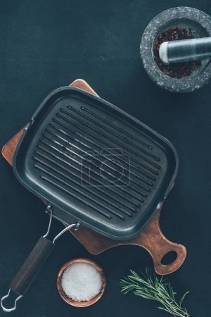 top view of empty grill pan with spices on black tabletop
