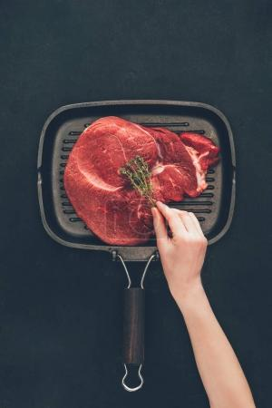 cropped shot of woman putting herb onto raw steak on grill pan