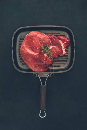 top view of raw steak with herb on grill pan