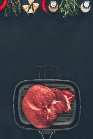 top view of raw steak on grill pan with spices on black surface
