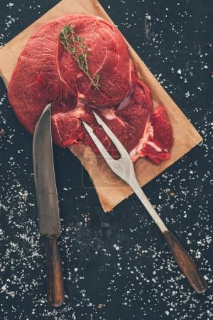top view of raw steak with fork and knife on wooden board