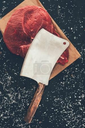 top view of raw steak with butcher cleaver on wooden board