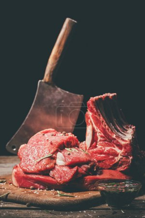 Photo for Various raw meat and cleaver on wooden cutting board - Royalty Free Image