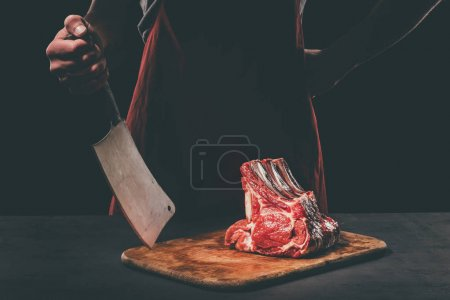 butcher with cleaver and raw meat on wooden cutting board