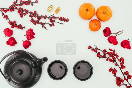 top view of chinese new year composition with tea and branches of berries isolated on white