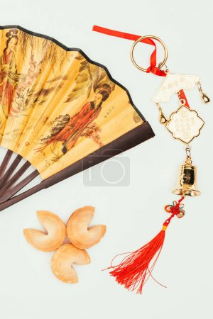 top view of traditional chinese handheld fan with talisman and fortune cookies isolated on white, Chinese New Year concept