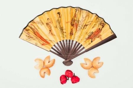 Photo pour Vue de dessus de ventilateur portatif chinois traditionnel avec des fleurs et des biscuits de fortune isolés sur blanc - image libre de droit