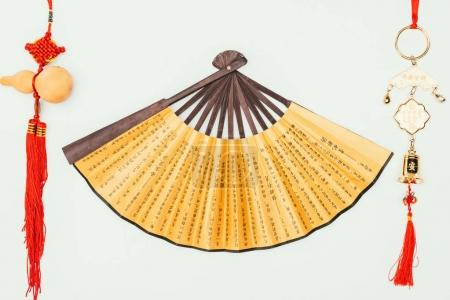 top view of traditional chinese handheld fan with talismans isolated on white