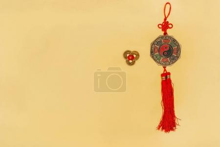 top view of chinese yin and yang talisman with coins on yellow