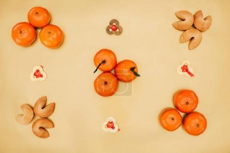 top view of chinese coins with tangerines and fortune cookies composition for new year