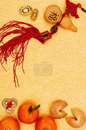 top view of traditional chinese talisman with tangerines and fortune cookies on golden surface, Chinese New Year concept