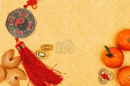 Photo pour Vue de dessus des talismans chinois avec mandarines et biscuits chinois sur la surface dorée, concept Nouvel An chinois - image libre de droit