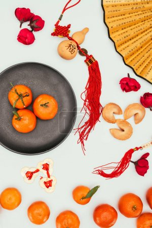 top view of chinese fortune cookies with tangerines and traditional talismans isolated on white, Chinese New Year concept