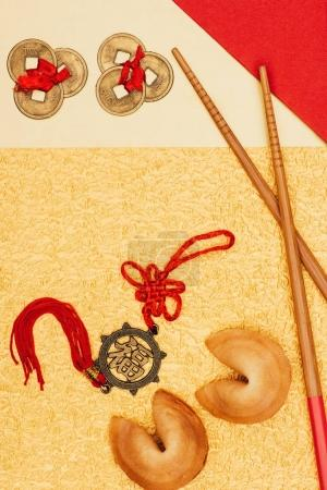 top view of chinese talismans with fortune cookies and chopsticks on golden surface, Chinese New Year concept