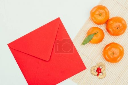 top view of red envelope with tangerines and chinese coins talisman, Chinese New Year concept