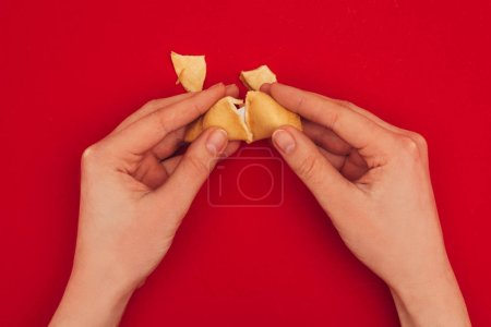 cropped shot of woman opening fortune cookie, Chinese New Year concept
