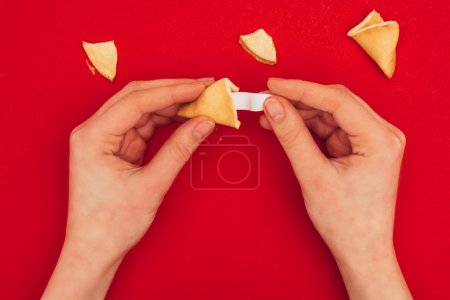 cropped shot of woman opening chinese fortune cookie, Chinese New Year concept
