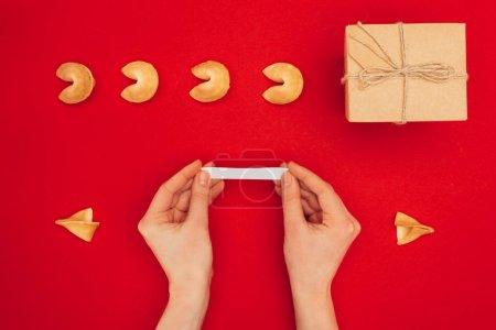 cropped shot of woman opening fortune cookie over red surface, Chinese New Year concept